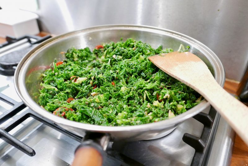 Cooking blanched kale with red chilli and garlic